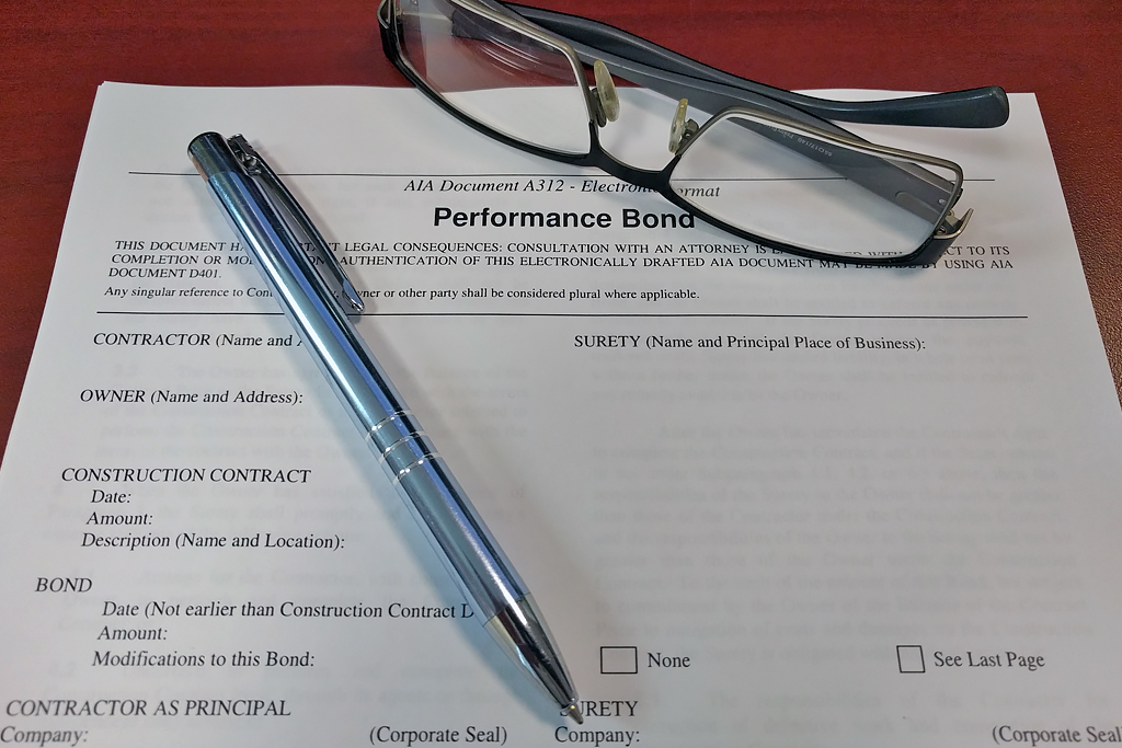 Pen and glasses laying over Performance Bonds document.