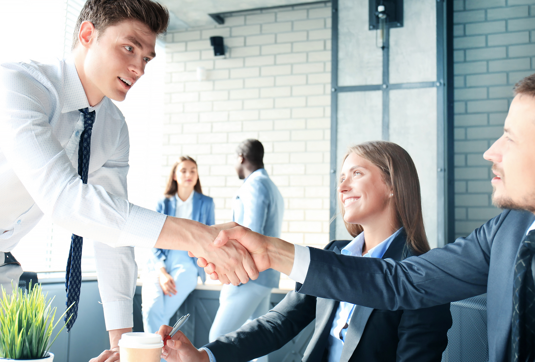 Two business professionals shaking hands as female professional looks on.